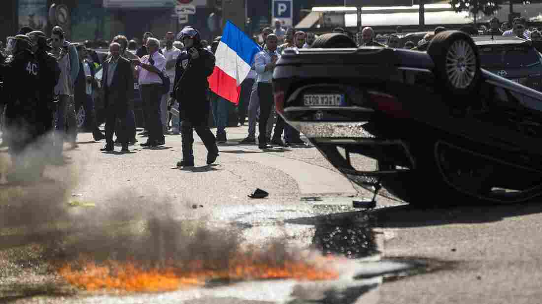 An UberPop vehicle was overturned by French taxi drivers, who also clashed with riot police, during Thursday's protest of the app-based ride-hailing company.