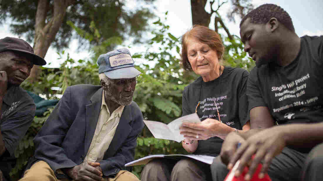 """Philip Cheruiyot (second from left) leans in to read the song titles on the CD booklet brought by Diane Thram. Cheruiyot's grandfather sang on Hugh Tracey's recording of """"Chemirocha II."""""""