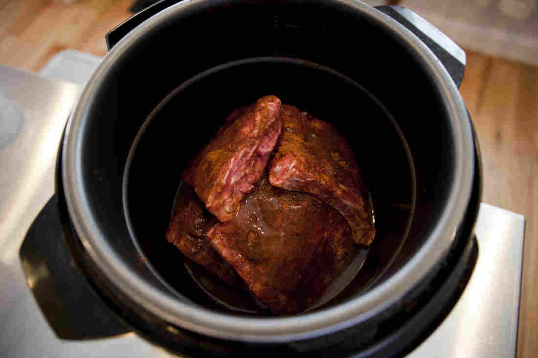 Place the ribs in the pressure cooker, arranged in a fan or teepee shape so that they'll fit and steam equally.