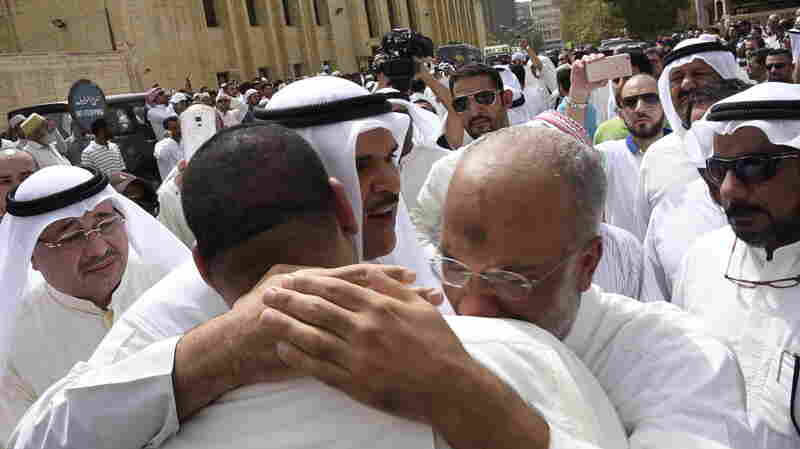 Kuwaiti Information Minister Sheikh Salman al-Humoud al-Sabah (center) consoles worshipers outside the Imam Sadiq Mosque after a suicide bomb attack following Friday prayers.