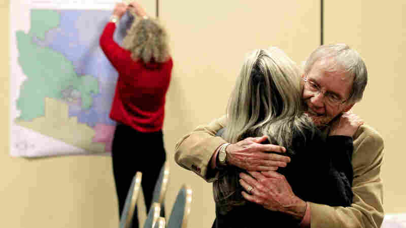 As a staff member takes down the Arizona redistricting map, Arizona Independent Redistricting Commission chair Colleen Mathis gets a hug from Frank Bergen, a Pima County Democrat, at a 2012 meeting.