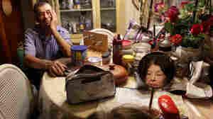 Arturo Martinez watches his wife, Aurora Martinez, put on makeup in their San Rafael, Calif., home. She has Alzheimer's.