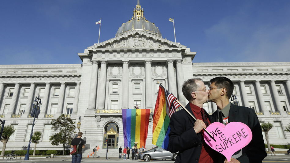 Gay rights advocates John Lewis (left), and his spouse Stuart Gaffney kiss across the street from City Hall in San Francisco, on Friday following a ruling by the U.S. Supreme Court that same-sex couples have the right to marry nationwide. (Jeff Chiu/AP)
