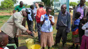 A woman in Yatta, Kenya, explains how to make clean water using a car battery and just the right mixture of salt and water.