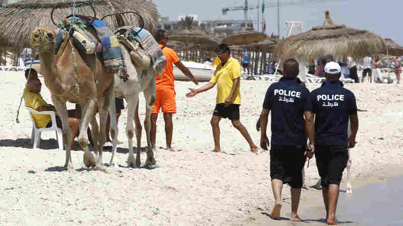 Police patrol the beach at Sousse, Tunisia, on Sunday. Tunisian authorities have deployed additional security forces, closed some mosques and banned some Islamist groups in the wake of Friday's terrorist attack at a beachfront hotel.
