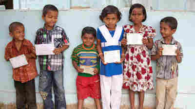 Children in Bangladesh display their birth registration cards.