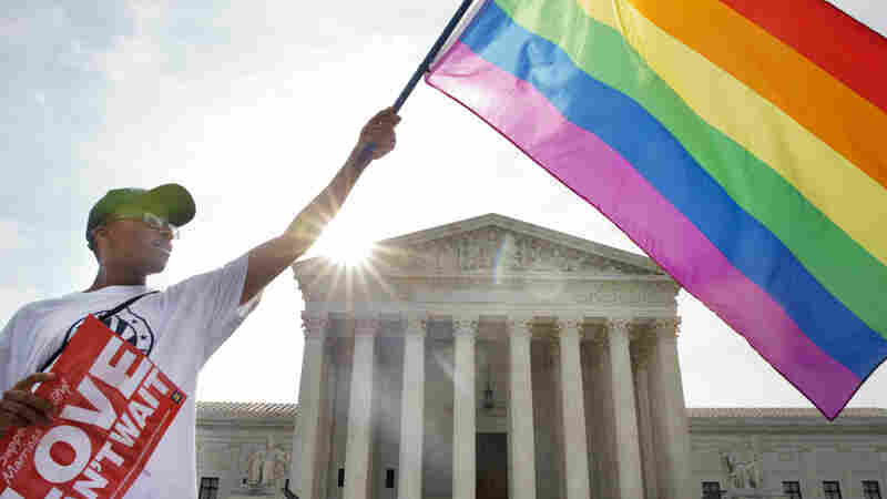Carlos McKnight waves a flag in support of same-sex marriage outside the Supreme Court.