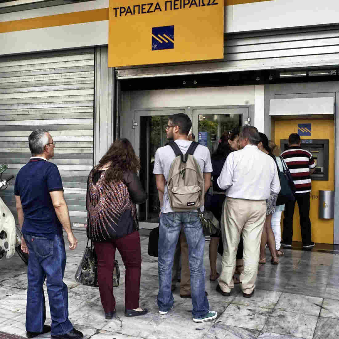People wait in line to withdraw euros from an ATM after Greece closed its banks Monday in Athens.