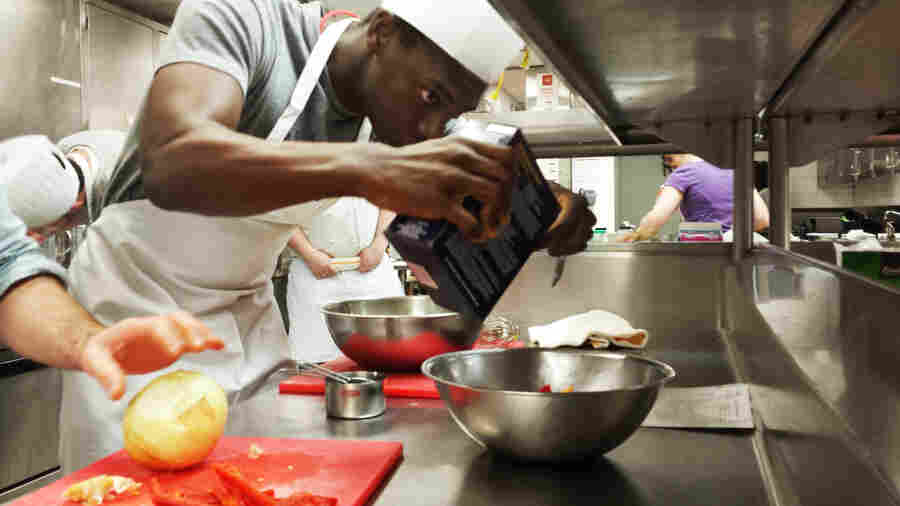 University of Chicago medical student Manny Quaidoo adds a pinch of salt to the spinach feta frittata he's learning to cook as part of a culinary medicine class.