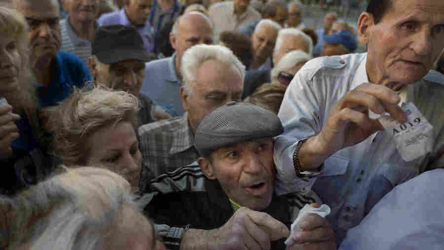 Customers holding their queue numbers try to enter a bank in Athens. The government ordered about 1,000 bank branches around the country to reopen Wednesday to help pensioners without ATM cards cash up to $134 from their retirement checks.