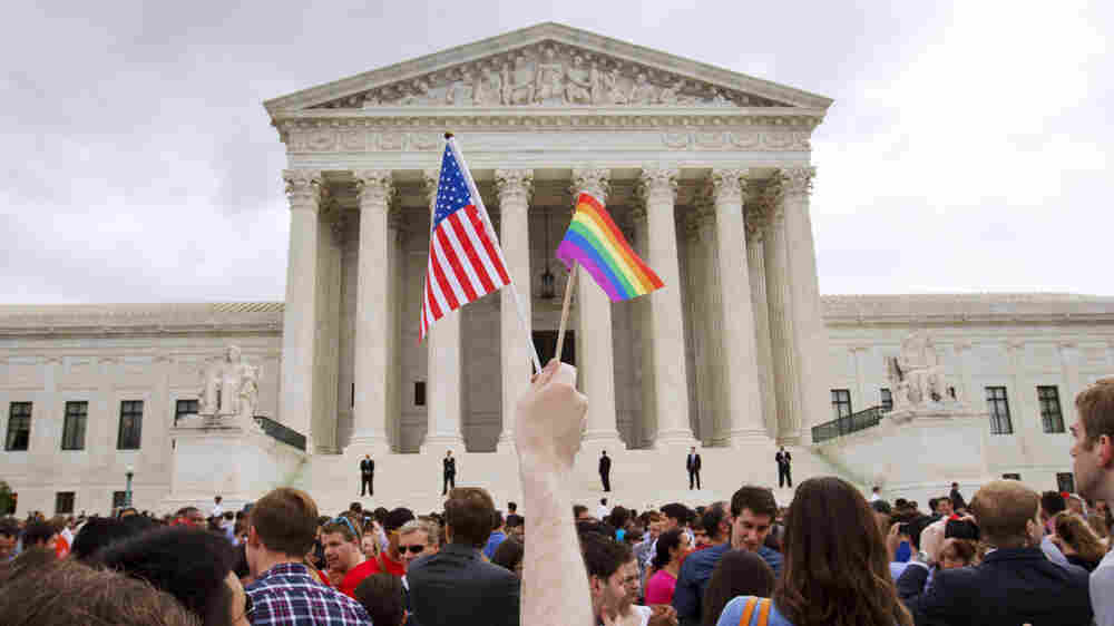 A man holds an American and a rainbow flag outside the Supreme Court in Washington, DC after the court legalized gay marriage nationwide.