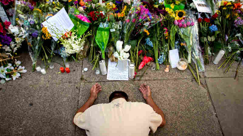Raymond Smith of Charleston, S.C., kneels in prayer in front of the Emanuel AME Church in Charleston before a worship service on June 21.