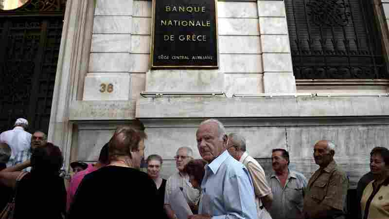 Pensioners queue outside a national bank branch in Athens on Thursday. Greek banks are running out of cash and the situation poses further danger to the economy, analysts say.