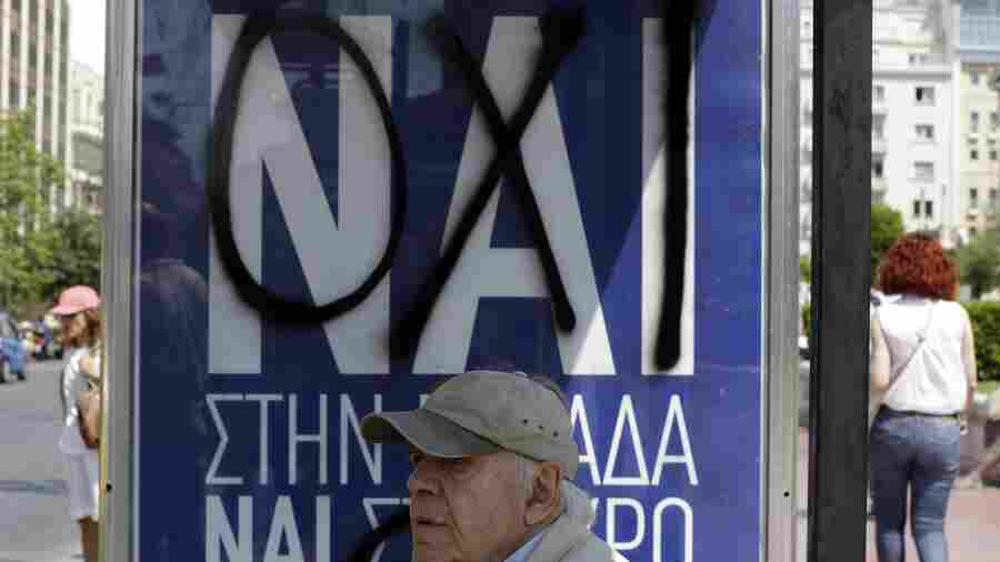 "A man waits at an Athens bus stop where the Greek word ""yes"" has been spray-painted over ""no"" on a banner put up in advance of Sunday's referendum. Greek voters will say whether they want to accept or reject a deal that's been offered by the country's creditors."