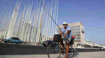 A fisherman cycles past the U.S. Interests Section building, behind right, in Havana in May.