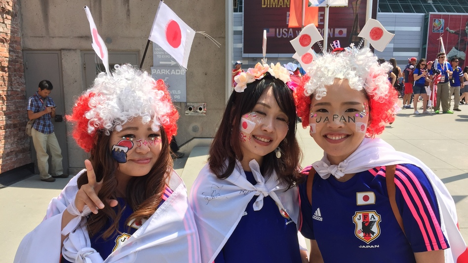 Japan fans are wildly outnumbered by red, white and blue ahead of the game on Sunday, but these three are decked out and ready to go. From left, Asuka Tsujimoto Keiko Tsujii and Yuri Nakayama came to Vancouver to cheer their country on. (Melissa Block/NPR)