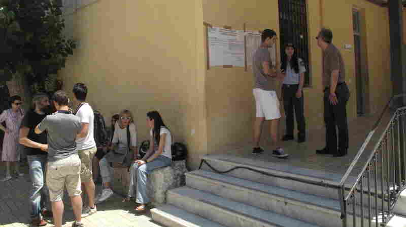 Greeks stand outside of a local school in Athens that served as a voting station.