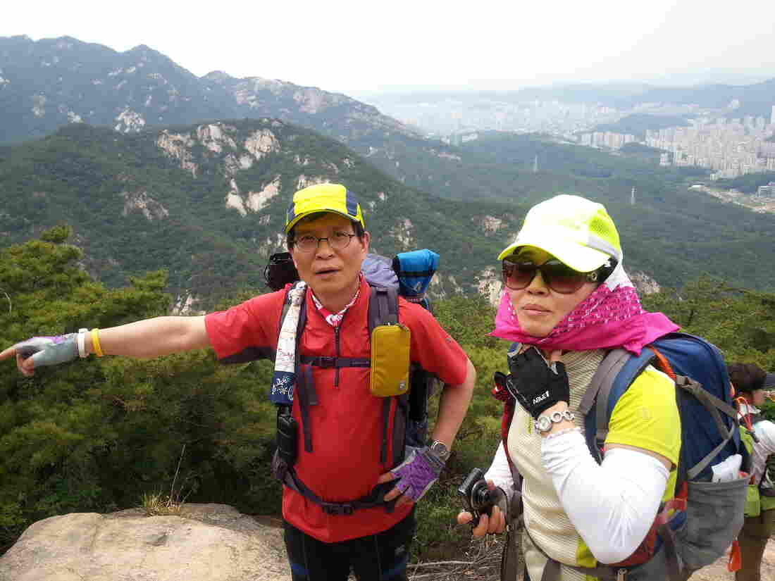 Hiking club leader Kang Seok-bong and hiker Lee Geun-rye atop Bukhansan Mountain, which overlooks Seoul. Kang says health permitting, he'll continue hiking into his 70s.