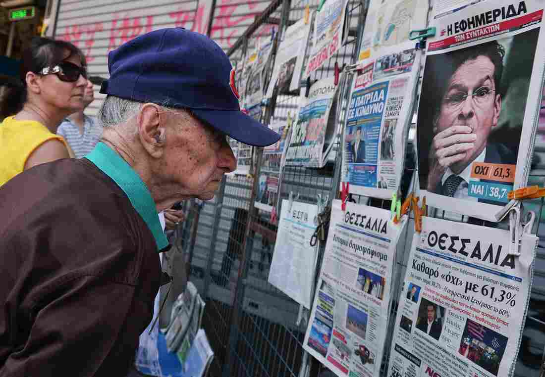People read newspaper headlines showing the results of Greece's referendum, in Athens on Monday.