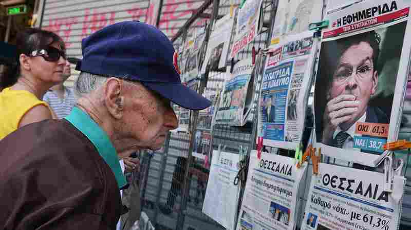People read newspaper headlines showing the results of Greece's referendum, in Athens, on Monday.