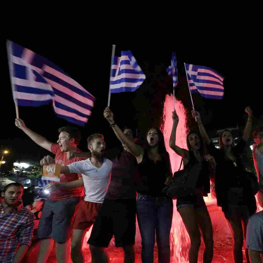 """Greek supporters of the """"no"""" vote celebrate at Syntagma Square in Athens on Sunday night after the results were announced. Greeks overwhelmingly rejected the demands of creditors for more austerity in return for rescue loans. But the country has no clear way out of its financial crisis."""
