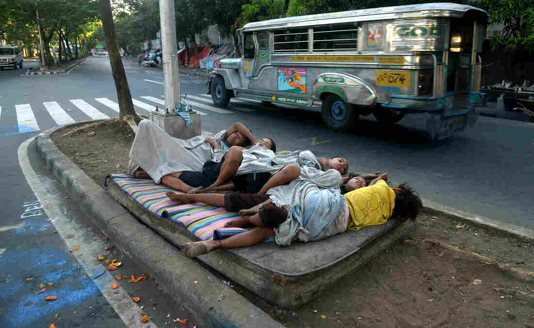 Street children sleep on a discarded mattress on a center island near a road crossing in Manila, Philippines, in April. After 15 years of the Millennium Development Goals, Asia as a region has had the fastest progress, reports the U.N., yet hundreds of millions of people there remain in extreme poverty.