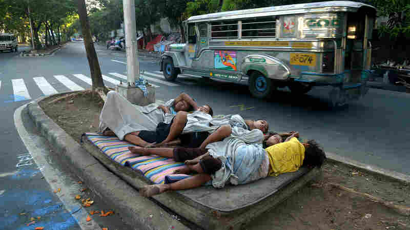 Street children sleep on a discarded mattress on a center island near a road crossing in Manila in April. After 15 years of the Millennium Development Goals, Asia as a region has had the fastest progress, reports the U.N., yet hundreds of millions of people there remain in extreme poverty.