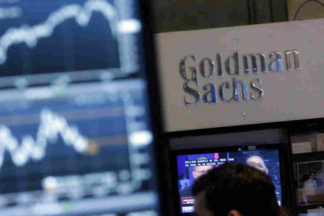 A screen at a trading post on the floor of the New York Stock Exchange is juxtaposed with the Goldman Sachs booth on Oct. 16, 2014.
