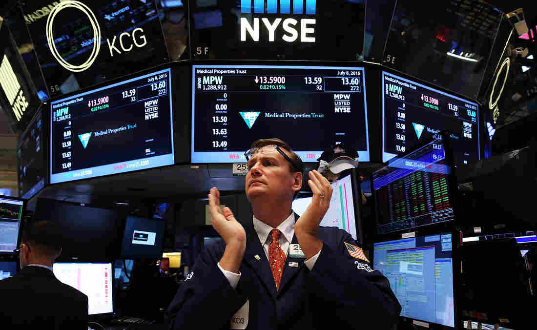 """A trader claps on the floor of the New York Stock Exchange at the close of the day after trading was paused for nearly four hours due to a """"technical glitch"""" on Wednesday."""