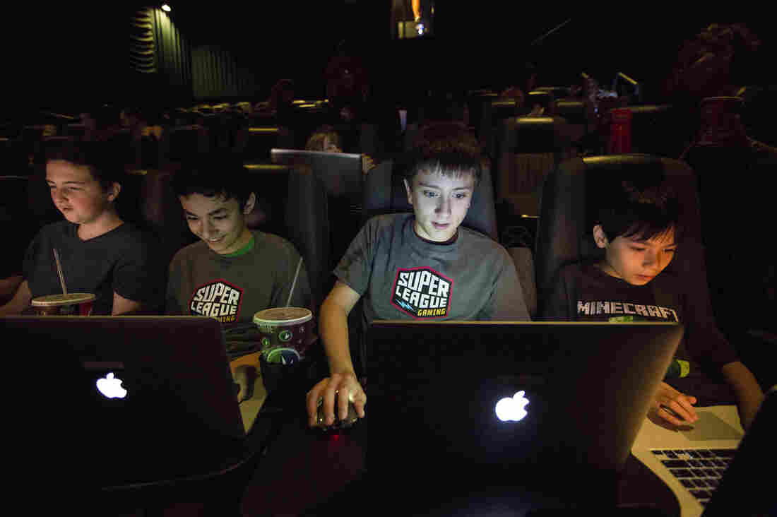 Tyler Hines (from left), Jaden Bautista, Eric Apfelbaum, and Justin Bautista play Minecraft together for the Super League Gaming event at Regal Cinemas on Monday in New York City. The players were able to build their own creations in Minecraft and battle each other while connected to the large movie theater screen.
