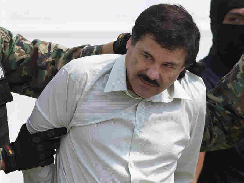 """In this Feb. 22, 2014, file photo, Joaquin """"El Chapo"""" Guzman is escorted to a helicopter in Mexico City, following his capture from his first prison escape. He was last seen on a prison surveillance camera Saturday night."""