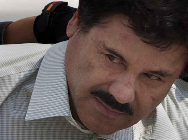 """Joaquin """"El Chapo"""" Guzman is escorted to a helicopter in handcuffs by Mexican navy marines at a navy hanger in Mexico City after his capture last year. Mexico's security now say Guzman has escaped from a maximum security prison for the second time."""