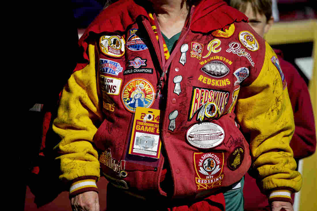 A Washington fan wears a patch-covered jacket on the sidelines before an NFL football game against the Tennessee Titans last year in Landover, Md.