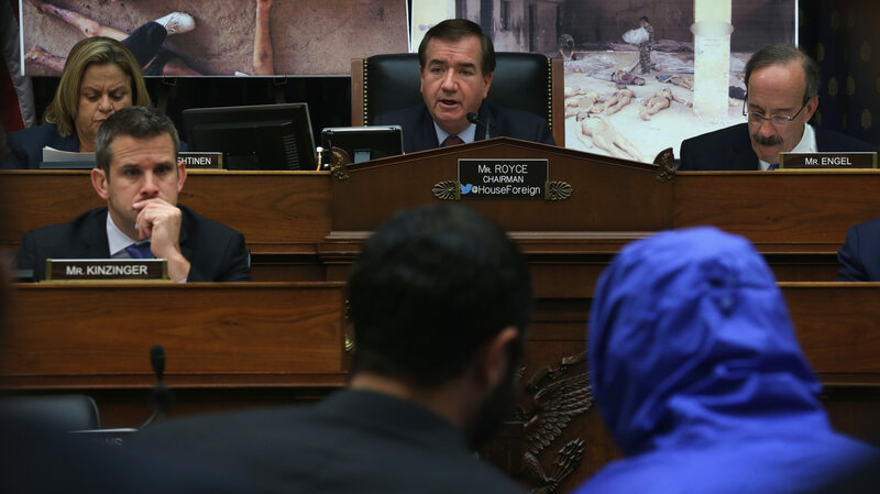 """Rep. Ed Royce (center), R-Calif., speaks during a July 2014 hearing of the House Foreign Affairs Committee, with """"Caesar,"""" a Syrian army defector who wore a blue, hooded jacket to protect his identity. Caesar smuggled out of Syria more than 55,000 photographs that document the torture and killings in Syrian prisons."""