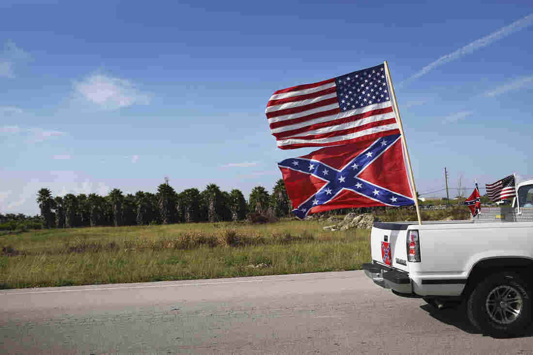 U.S. and Confederate flags fly from a vehicle during a rally to show support for the flags on July 11 in Loxahatchee, Fla.