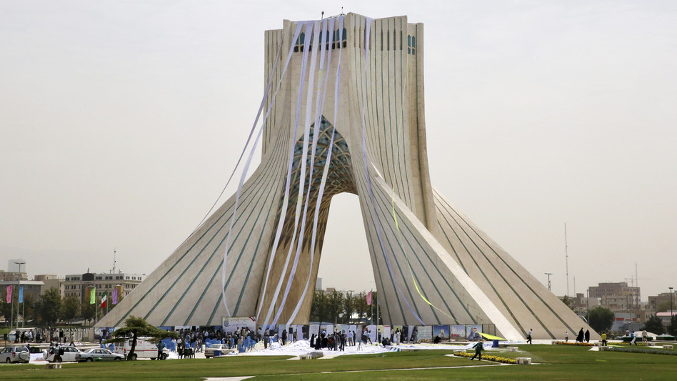 """Iranian hard-liners hang petitions from the Azadi (Freedom) Tower in Tehran during a June 30 demonstration demanding a """"good deal"""" in the nuclear negotiations between Iran and six world powers. Negotiators announced a deal Tuesday morning in Vienna. (Vahid Salemi/AP)"""