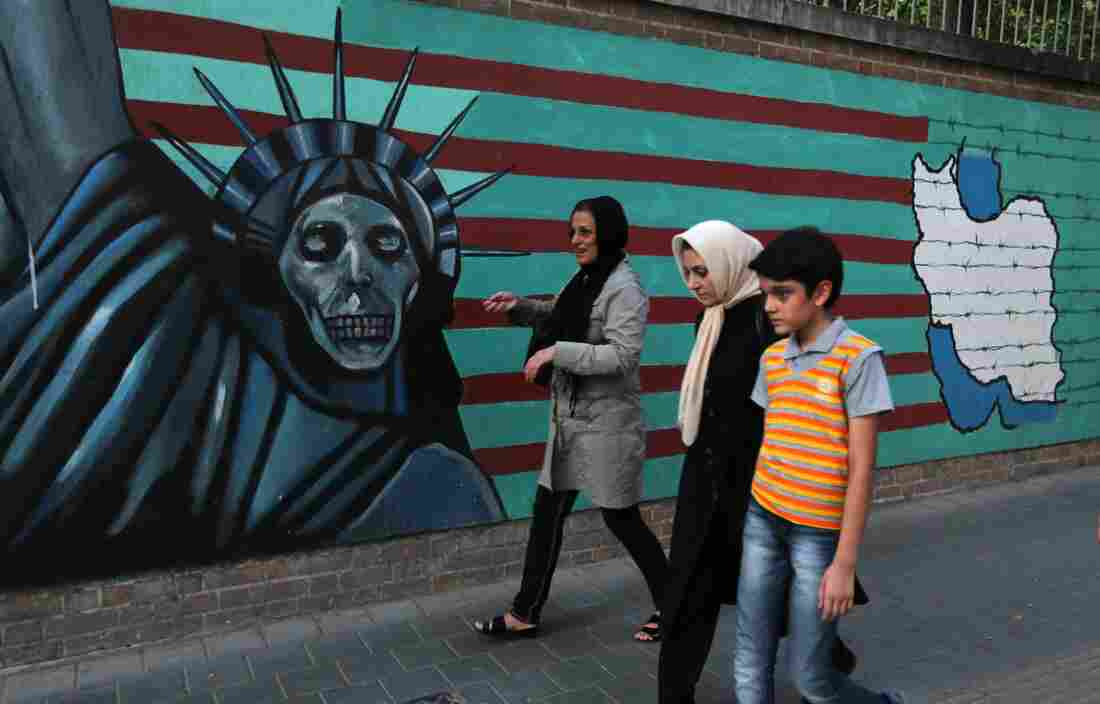 "An Iranian family walks past anti-U.S. graffiti on the wall of the former U.S. embassy in Tehran on Tuesday. President Hassan Rouhani told Iranians that ""all our objectives"" have been met by a nuclear deal agreed upon Tuesday after talks with six world powers, including the U.S."