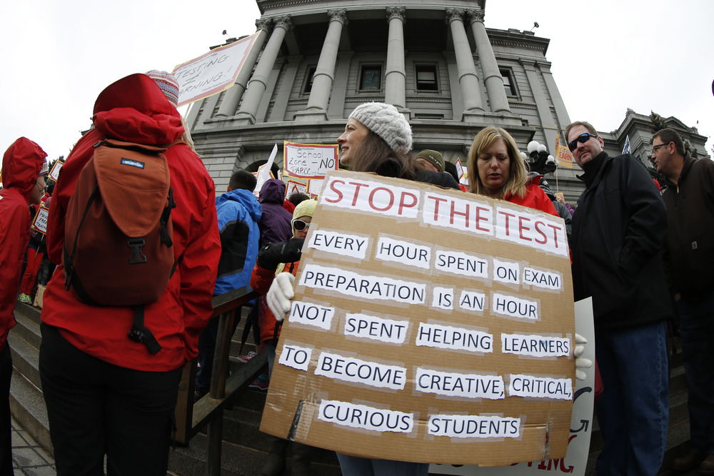 Colorado: Teacher Jen Shafer of Colorado Springs, Colo., waves a placard during a rally against what protesters called