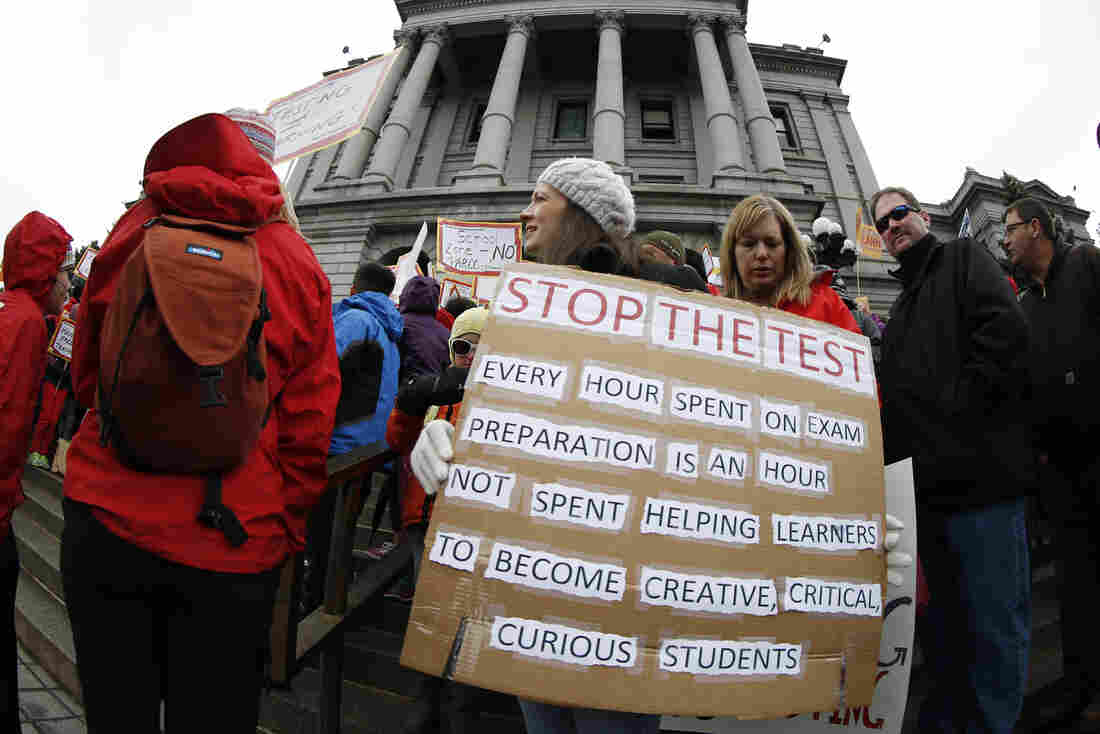 """Colorado: Teacher Jen Shafer of Colorado Springs, Colo., waves a placard during a rally against what protesters called """"excessive"""" standardized testing in Colorado schools on the west steps of the Capitol in Denver."""
