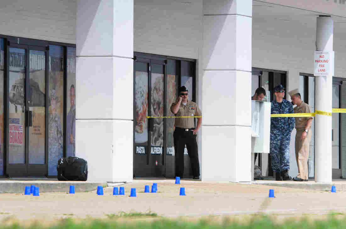 Reserve Recruitment personnel stand outside a military recruiting center on Lee Highway in Chattanooga, Tenn., as the area is cordoned off with blue shell casing markers. Officials said two military facilities in Tennessee were attacked in shootings Thursday.