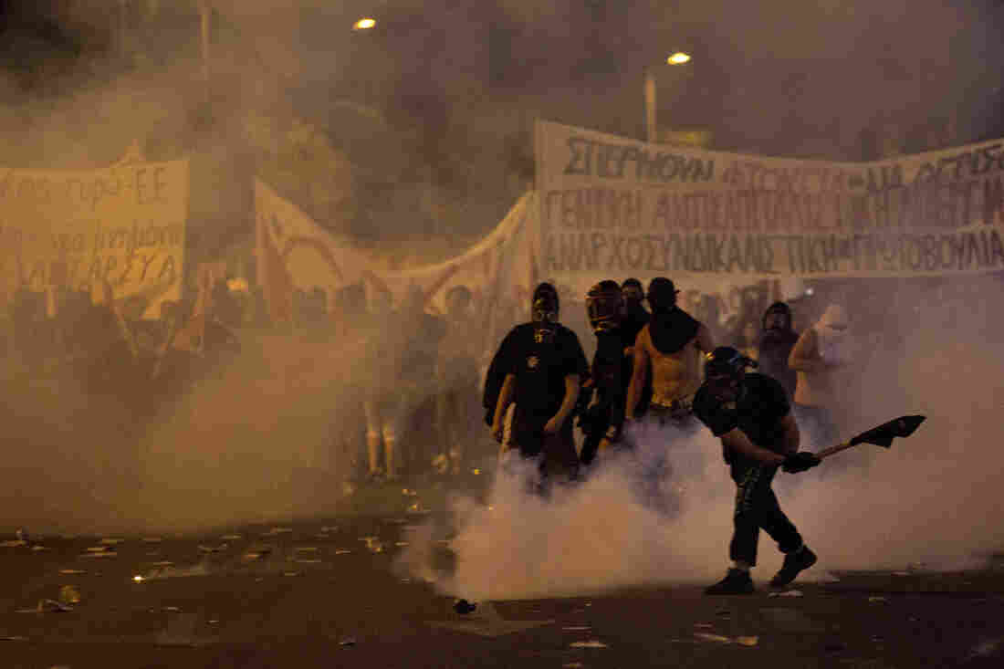 An anti-austerity protester pushes away a tear gas canister thrown by riot police during clashes in Athens on Wednesday.