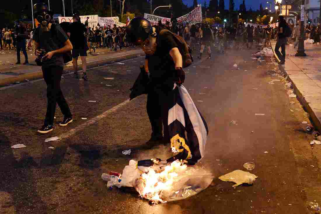 A protester burns a Greek flag in central Athens, during an anti-austerity protest on Wednesday.