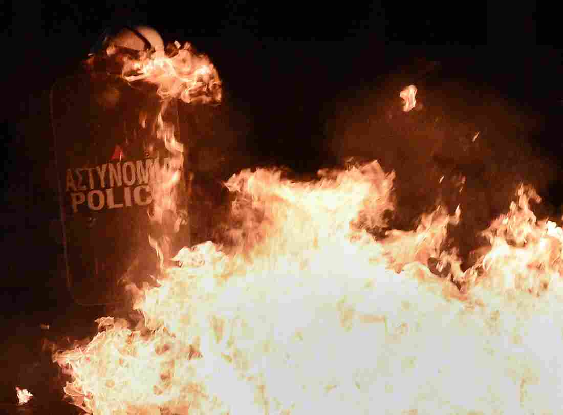 Riot police use their shields against petrol bombs lobbed by protesters during an anti-austerity protest on Thursday.