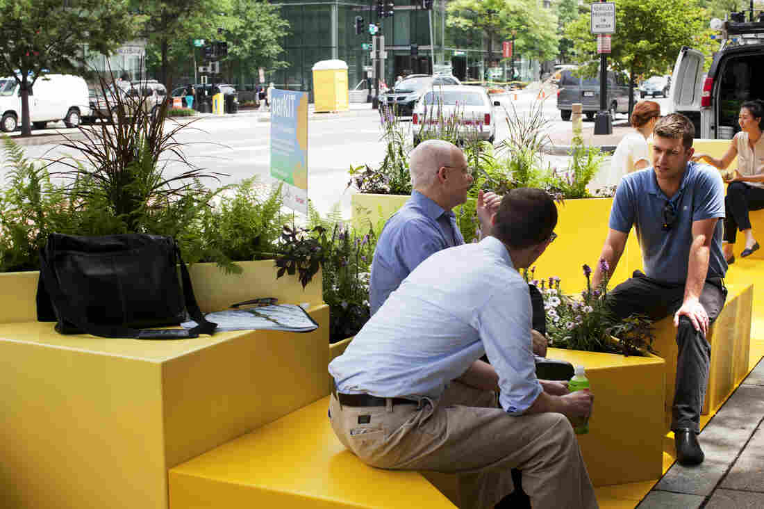 Will Handsfield (right), transportation director for the Georgetown Business Improvement District, talks with other parklet visitors in Washington, D.C. The Georgetown neighborhood hopes to have a parklet by September, and other areas may follow suit.