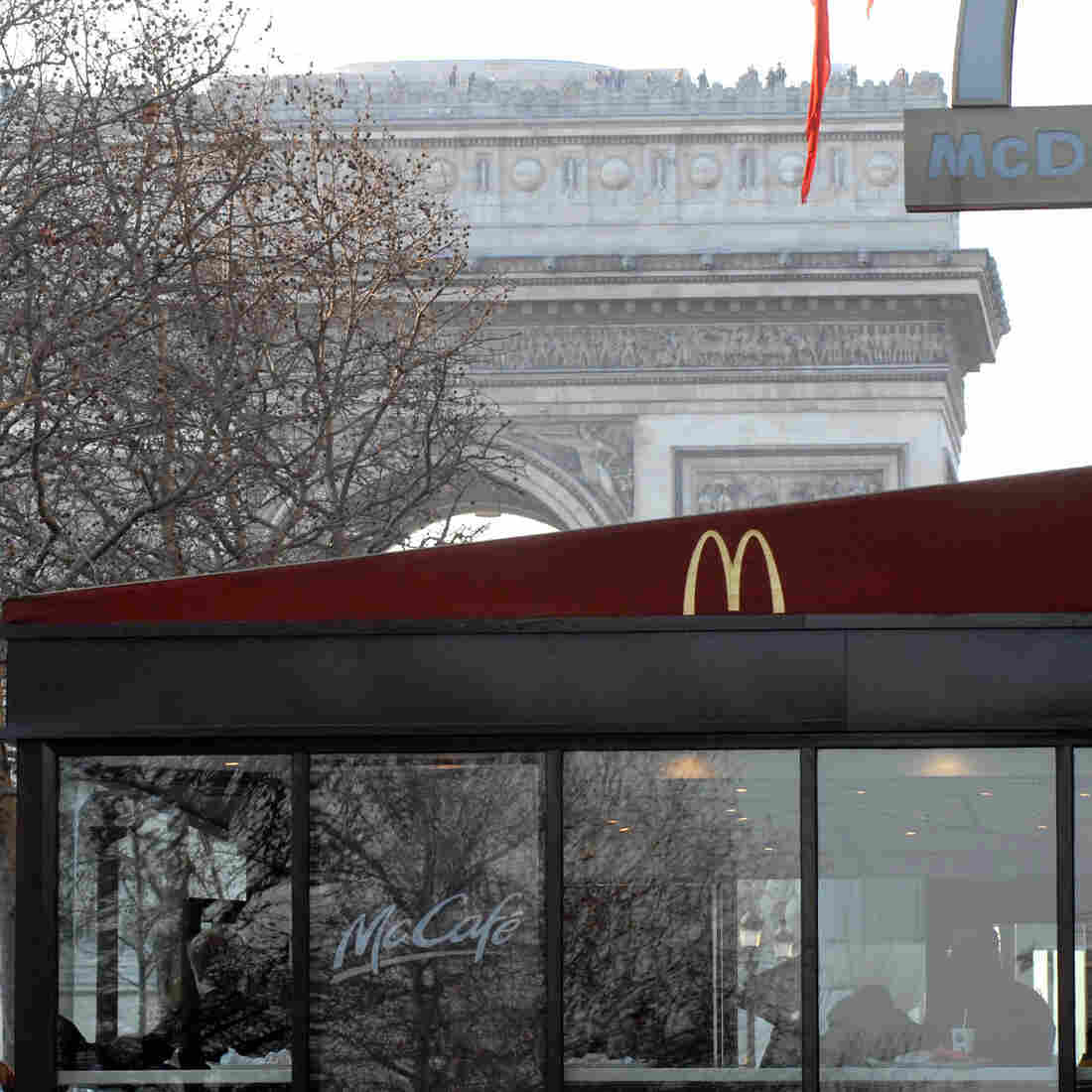 """The Arc de Triomphe is visible behind a McDonald's restaurant on the Champs Elysees in Paris, France. The nation is now McDonald's second-biggest market, but one historic neighborhood known as """"the belly of Paris"""" has pledged to keep it out."""