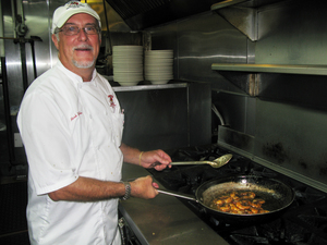 Co-owner and chef Mark DeFelice cooks up an order of barbecue shrimp at Pascal's Manale restaurant in New Orleans.