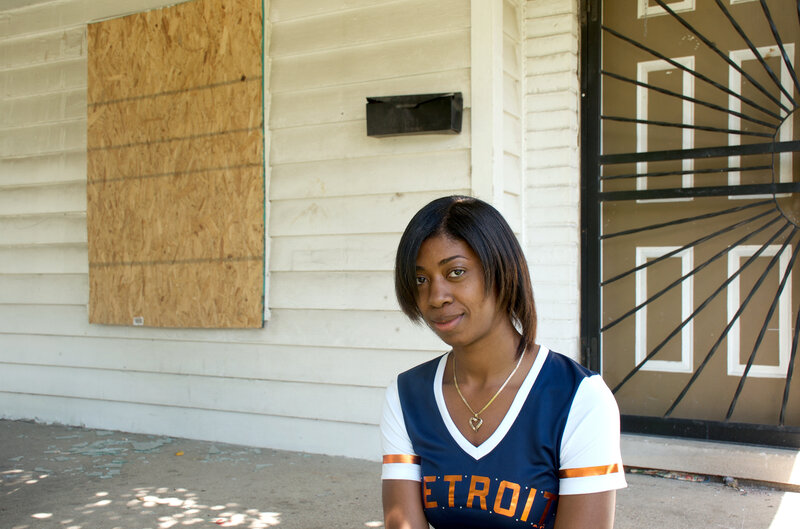 Lanita Carter sits on the porch of the home she purchased in Detroit.