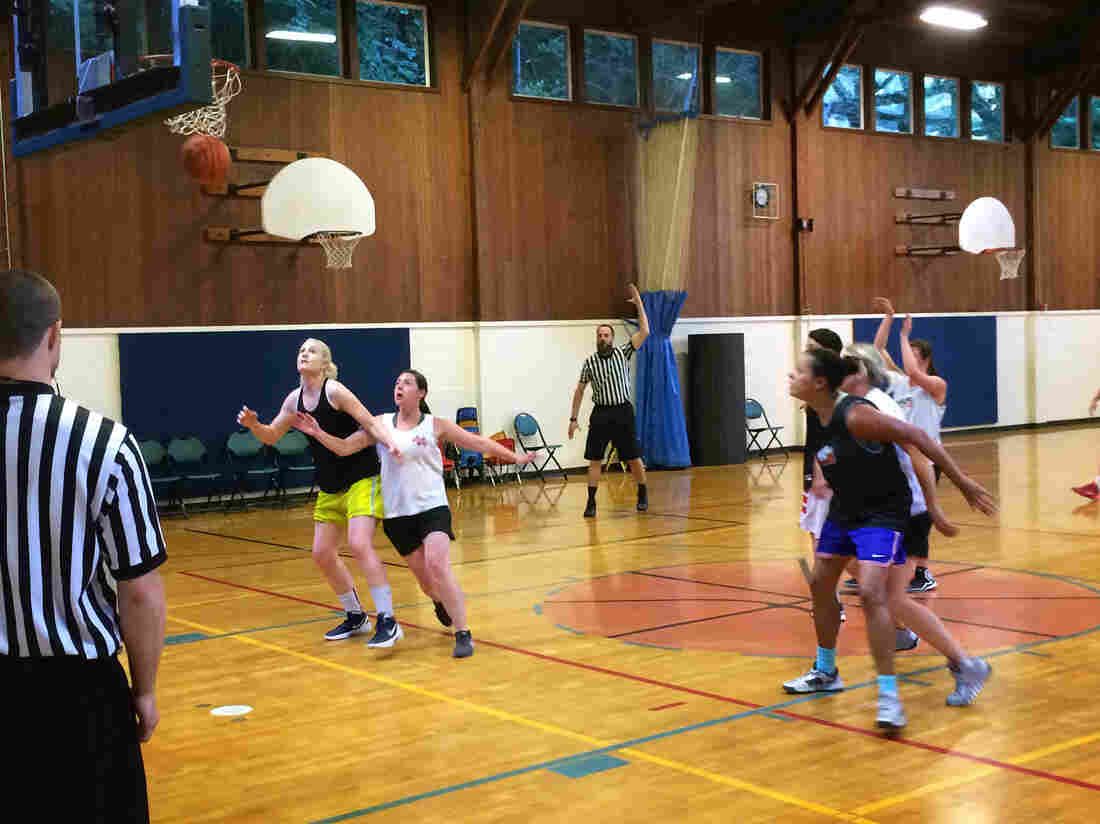 Lei Hart, in black jersey and blue shorts, boxes out an opponent on a free throw attempt. Hart, 41, plays every Monday night at the Hillside Community Center in Portland, Ore.