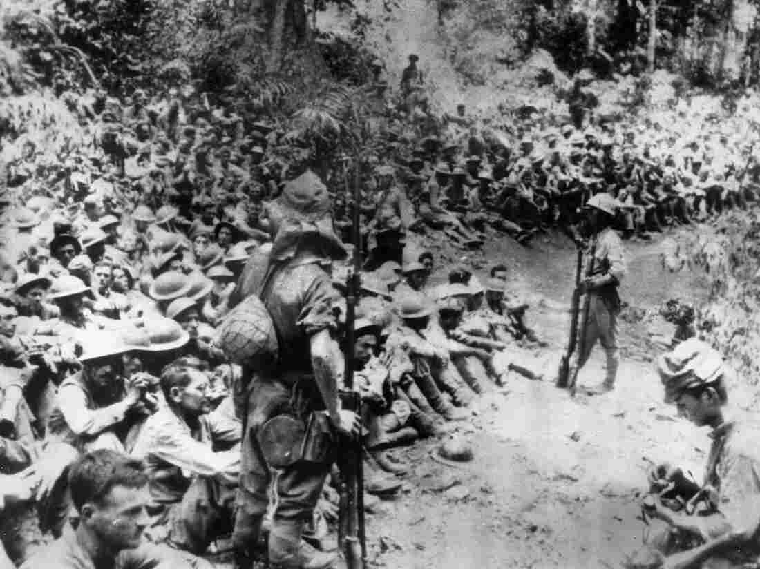 In this 1942 file photo provided by the U.S. Marine Corps, Japanese soldiers stand guard over American prisoners of war just before the start of the Bataan Death March following the Japanese occupation of the Philippines. Some of those who survived the death march were later forced to work for Japanese industry.