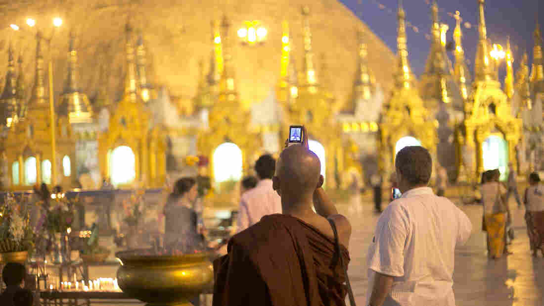 A Buddhist monk takes a photo on his phone at Shwedagon Pagoda in Yangon, Myanmar.